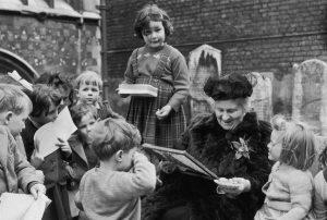 Maria Montessori acompañada de niños